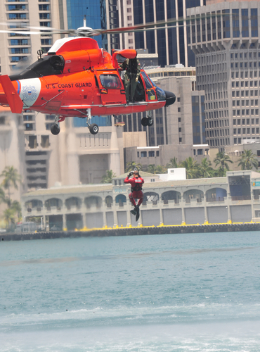 Coast Guard Petty Officer 1st Class Matthew Thiessen gets lifted into the MH-65 Dolphin helicopter after a search and rescue demonstration for National Safe Boating Week in Honolulu Harbor, May 20, 2011. In support of National Safe Boating Week a press briefing was held at Station Honolulu where local agencies joined the Coast Guard to promote the kickoff.