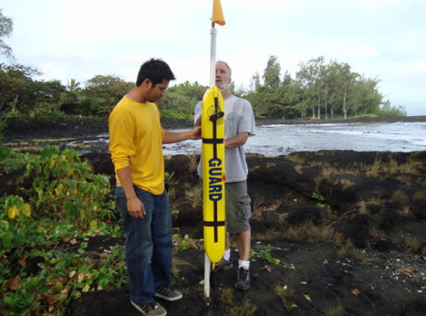 Rotary Club of South Hilo members Dayle Tejada (L) and Gene Hennen finish installing the first donated rescue tube Thursday at Lehia Beach Park in Hilo.