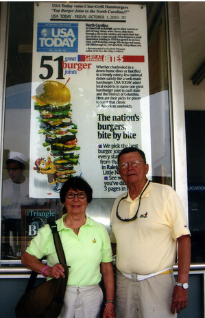 "Doris and Joe Lindner pose by the USA Today poster at the Char-Grill in Raleigh, N.C. During the past two years, the couple â€"" retired doctors living on Hilton Head Island â€"" have driven to all but one of America's ""51 Great Burger Joint"
