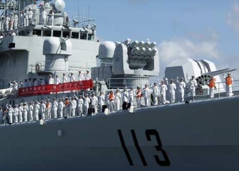 In this U.S. Navy file photo, sailors aboard the Chinese People's Liberation Army-Navy destroyer Qingdao (DDG 113) wave as the ship departs Pearl Harbor following a routine port visit in September 2006.