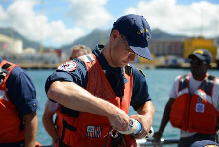 Coast Guard Petty Officer 1st Class James Moore with the National Strike Force Atlantic Strike Team, prepares a water quality instrument used to monitor depleted oxygen and pH levels in the Honolulu Harbor, Honolulu, Sept. 15, 2013. Personnel from the Coast Guard, U.S. Environmental Protection Agency, U.S. Fish and Wildlife, National Oceanic and Atmospheric Administration tested the water at various locations around Honolulu Harbor affected by the molasses spill. (U.S. Coast Guard photo by Petty Officer 3rd Class Tara Molle)