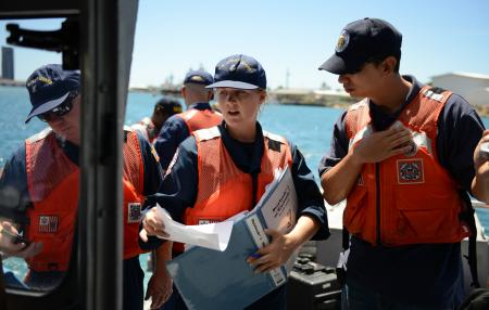 Crewmembers from the Coast Guard National Strike Force discuss data from a water quality instrument used to monitor depleted oxygen and pH levels with a member of the state of Hawaii Department of Health in Honolulu Harbor, Honolulu Sept. 15, 2013. Personnel from the Coast Guard, U.S. Environmental Protection Agency, U.S. Fish and Wildlife, National Oceanic and Atmospheric Administration tested the water at various locations around Honolulu Harbor affected by the molasses spill. (U.S. Coast Guard photo by Petty Officer 3rd Class Tara Molle)