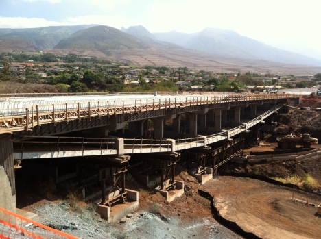 The new bridge, seen above under construction, utilizes an inverted tier arch design, which places arched support beams below the road surface rather than above.  This design was selected to minimize obstructions of ocean views for motorists and the Lahaina community.