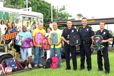 Hope Services Hawaii workers pick up backpacks from Officer Jason Grouns, Chief Harry Kubojiri and Officer Patrick Menino at the Hilo police station, one of eight collection sites around the island.