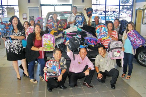 Kama'aina Motors employees display a truckload of backpacks their company collected after payroll clerk Ashley McCollum-Ranne (at far left) heard an announcement on the radio.