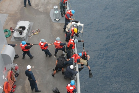 Crew members aboard the dock landing ship USS Pearl Harbor (LSD 52) recover a bale of marijuana found adrift in the Pacific. Pearl Harbor is currently underway conducting training exercises off the coast of Southern California. (U.S. Navy photo)