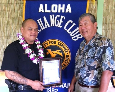 Aloha Exchange Club Director Curtis Chong presents an 'Officer of the Month' certificate to Officer Jeremy Kubojiri.