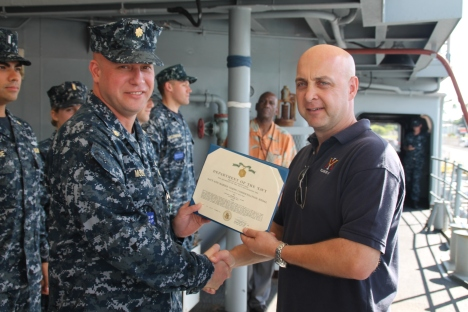 The Commander gives Lt. Noonen a certificate for his time aboard the ship.