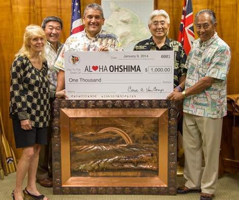 Carol Van Camp of the Japanese Chamber of Commerce & Industry of Hawai'i presents a $1,000 donation from the chamber to the Aloha Ohshima relief drive. Van Camp is joined by Honorary Consul General of Japan Art Taniguchi, Hawai'i County Mayor Billy Kenoi, and Hiroshi Suga and Tommy Goya of the Japanese Community Association of Hawai'i. Also pictured is Ohshima's 50th anniversary gift to Hawai'i County, a copper piece crafted by a 19th-generation craftsman assisted by the people of Ohshima.