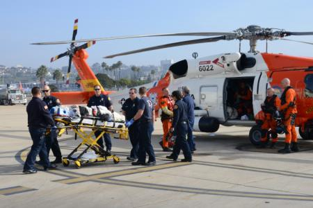 An aircrew from U.S. Coast Guard Sector San Diego transfers an injured woman to emergency medical personnel after medically evacuating her from a cruise approximately 150 miles west of San Diego, Jan. 23, 2014. The 69-year-old woman fell down a stairwell and suffered possible head injuries and internal bleeding. (U.S. Coast Guard photo by Petty Officer 1st Class Henry G. Dunphy)