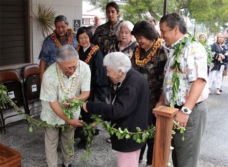 Glenn Yano and former State Rep. Virginia Isbell untie the maile lei to reopen Yano Hall. Looking on is Managing Director Wally Lau, Reverend Jiko Nakade, Councilmembers Dru Mamo Kanuha and Brenda Ford, Kona Regional Senior Club President Sharen Bangay, and Mayor Billy Kenoi.