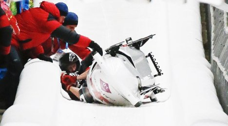 Canada's pilot Justin Kripps, Jesse Lumsden, Cody Sorensen and Ben Coakwell are assisted as their sled flips during the four-man bobsleigh event at the Sochi 2014 Winter Olympics, at the Sanki Sliding Center in Rosa Khutor February 22, 2014. (REUTERS)