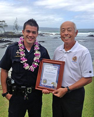 "Hilo Exchange Club board member Joey Estrella presents an ""Officer of the Month"" award to John Balberde"