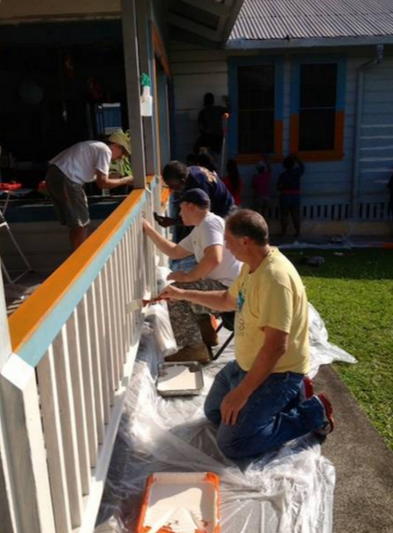 Rotary Club of Hilo members painting the preschool center at the YWCA of Hawaii Island.
